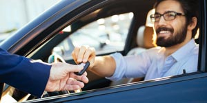 Man in rental car taking key from agent